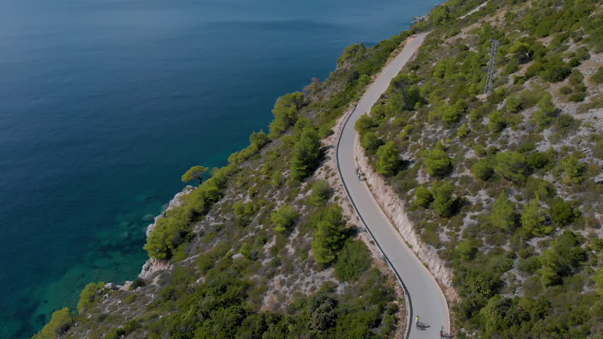 Aerial view from drone of bicycles riding along a beautiful mediterranean coastal road.   Shutterstock HD Video #1027384478