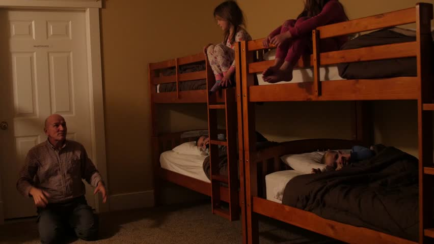Little kids listen to grandpa tell a story while sitting in bunkbeds in a large room during a sleep over