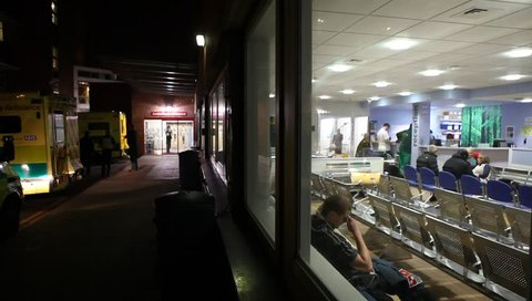 LONDON, UK - 2019: NHS A and E exterior night as man waits in reception