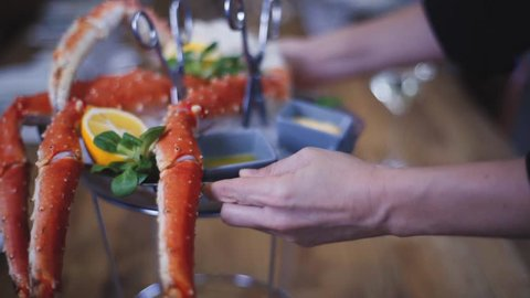 A dish with a crab is placed on the table.  Crab lies on ice in a dish with lemon and basil. Beautiful crab feed on ice. A dish of crab stands on a wooden table in a restaurant.