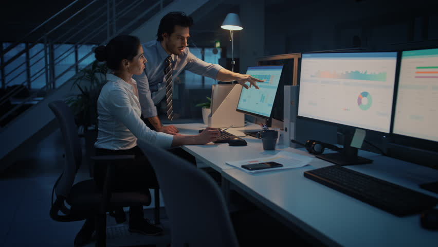 Late at Night In Modern Office: Businessman and Businesswoman Work on Desktop Computer, Having Discussion, Finding Problem Solution, Finishing Important Project. Successful Responsible Office Workers | Shutterstock HD Video #1027448438