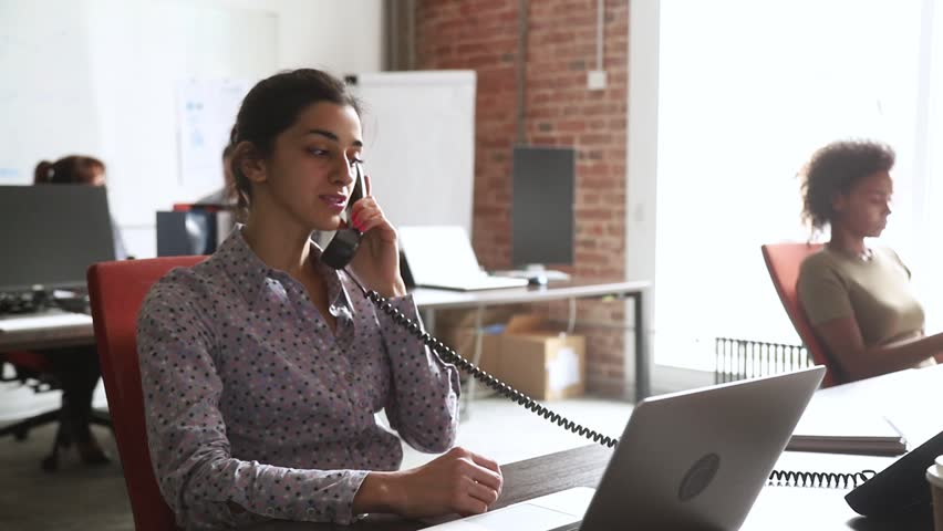 Young indian businesswoman talking on the phone consulting client in corporate office, focused hindu sales manager worker sitting at work desk with laptop making telephone call selling services