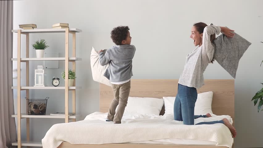 Happy african american mixed race family mom baby sitter and little son having fun pillow fight on bed, young mother nanny laughing playing funny game with small child boy in bedroom on leisure time | Shutterstock HD Video #1027488458