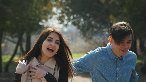 Positive boy jumped to his girlfriend in cadre in the park. Funny young couple on the nature