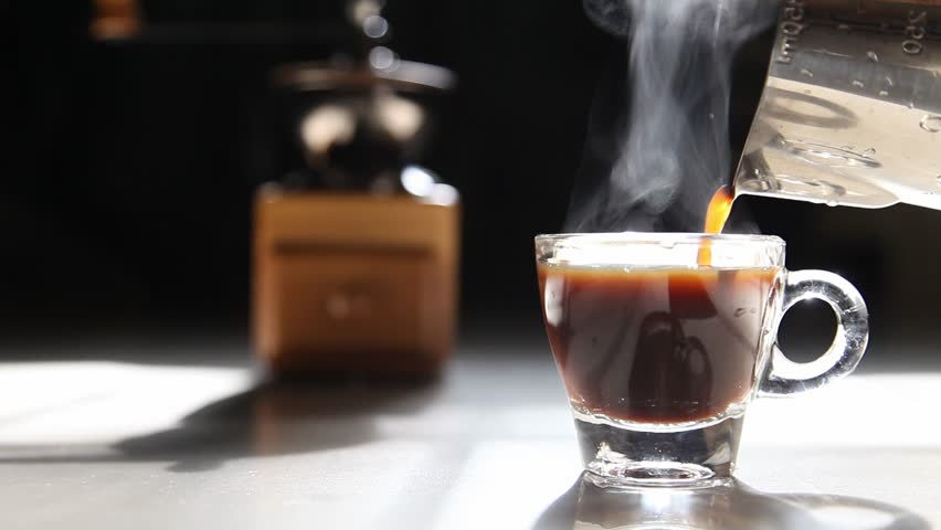 Traditional home brew espresso coffee pouring into a small cup with grinder on the dark background by the morning light with copy space | Shutterstock HD Video #1027549058