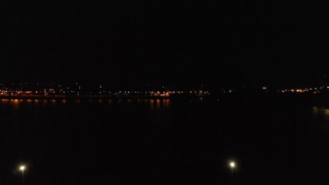 Beautiful sea embankment with a line of lampposts and houses at night