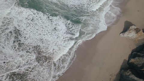 Aerial birds eye drone view top downing across sandy ocean coastline of South Pacific Highway. Rocky mountainous green terrain with waves crashing against shoreline.