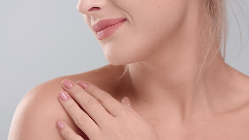 Close-up beauty portrait of young woman touching her smooth skin in collarbone area against grey background   skin care concept   Shutterstock HD Video #1027606118