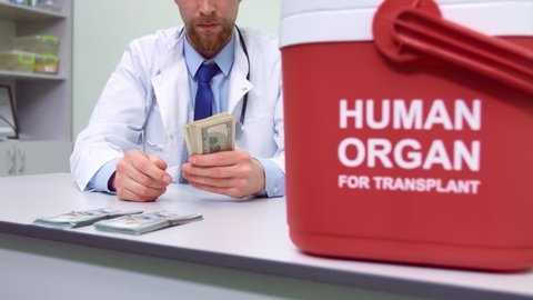 Male doctor in white coat sitting in his office and counting ready money at the background of organ trafficking container   Illegal human organ trade concept.