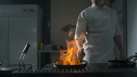 Chef fires up the flambe on a hot pan at the kitchen in slow motion, big open fire in the kitchen, pan on fire, cooking on the open flame, 4k UHD 60p Prores HQ 422