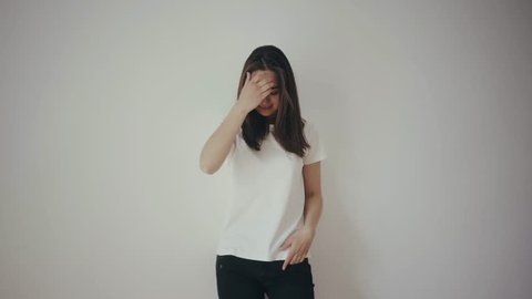 Pretty young hipster girl wearing blank white t-shirt and black jeans, mock-up of blank t-shirt, white isolated background, happy smiling and dancing, laughing and turning around with front and back