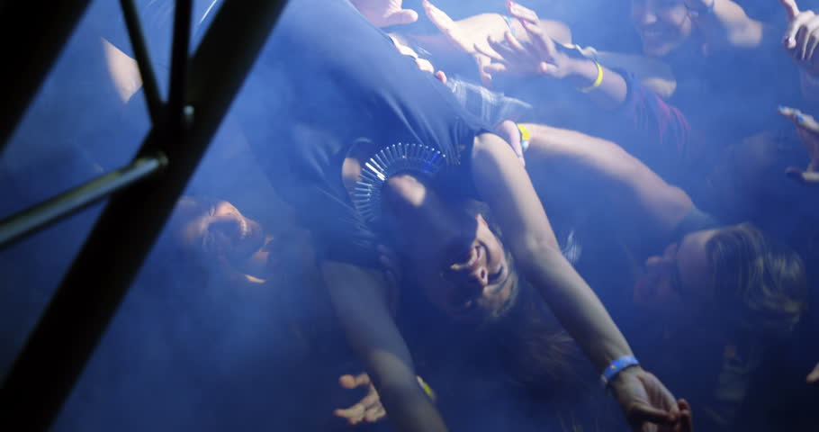 Overhead view of Caucasian woman crowd surfing at a concert in nightclub. | Shutterstock HD Video #1027648238