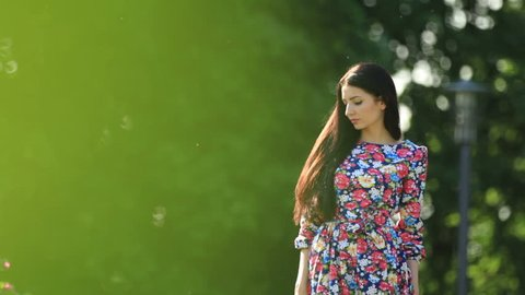 Young girl model brunette walking in the park. The beautiful long dress. Close median overall plans. The beautiful nature and the beauty of the girl.