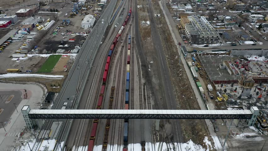 Aerial view of train yard and Denver skyline.   Shutterstock HD Video #1027686938