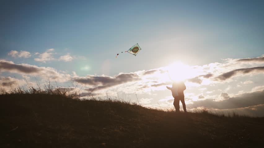 Happy family father and child daughter launch a kite on meadow at sunset. Funny family time. Concept of friendly family, travel and freedom. | Shutterstock HD Video #1027705058