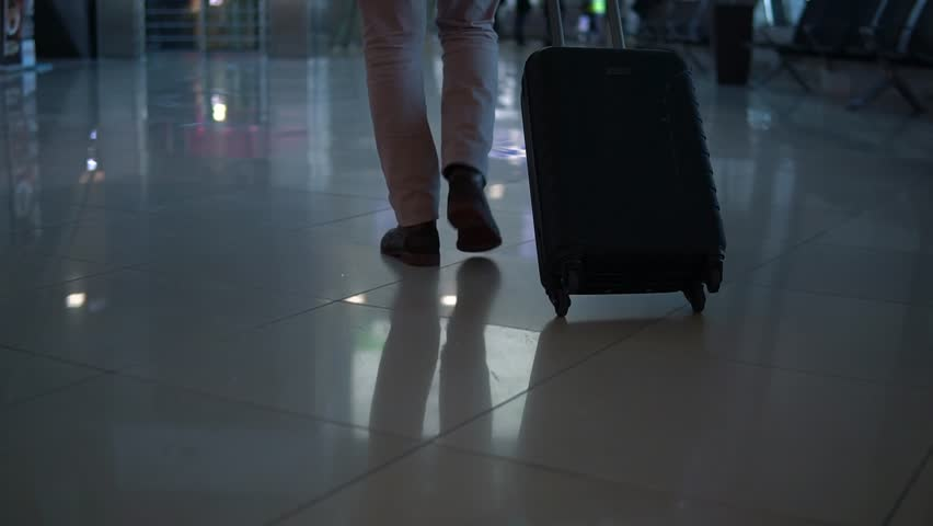 Close up shot of man legs with the baggage walking to the airport terminal. | Shutterstock HD Video #1027707818