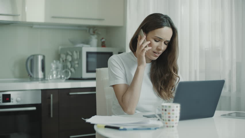 Sad woman using phone at home workplace. Upset woman talking mobile phone at home office. Stressed freelancer working at home kitchen. Female person using smartphone. Unhappy girl call phone   Shutterstock HD Video #1027710668