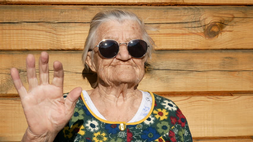 Brutal granny in sunglasses waves by hand at the camera. Wrinkled face of aged woman. Grandmother on wooden rustic background. Old granny looks into the camera and waves by hand. 91 year old granny. | Shutterstock HD Video #1027713308