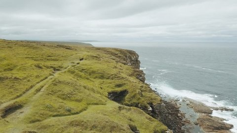 Aerial drone shots of beautiful steep cliffs at the coast of North Scotland with the rough sea throwing massive waves against the rock wall and many seabirds nesting in the cliffs