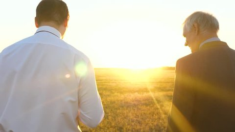 Businessman and farmer negotiate at sunset in field. teamwork men on a business project. Business meeting of business men in the park.