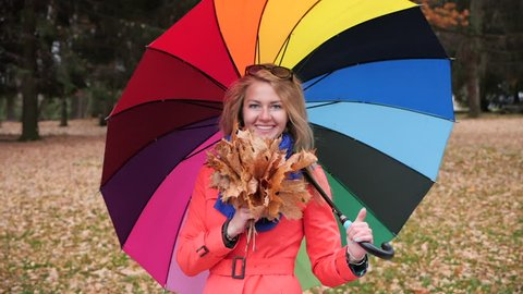 Slow motion. A young pretty longhaired blonde girl with a large colourful umbrella in a red coat in the autumn park turns around and smiles at the camera holding a bouquet of yellow maple leaves.
