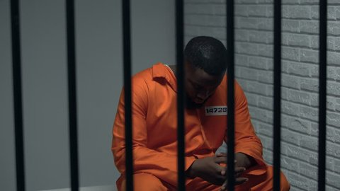 Thoughtful black prisoner sitting in cell, human rights protection, imprisonment