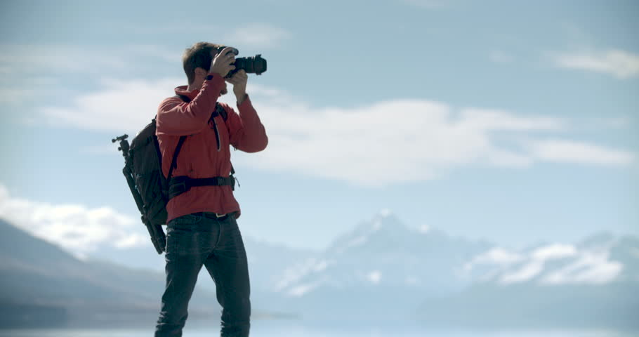 Young adventure photographer taking photographs in New Zealand. Lake with Mt Cook in background. Video clip recorded on professional camera, 10bit Pro Res in slo-motion.