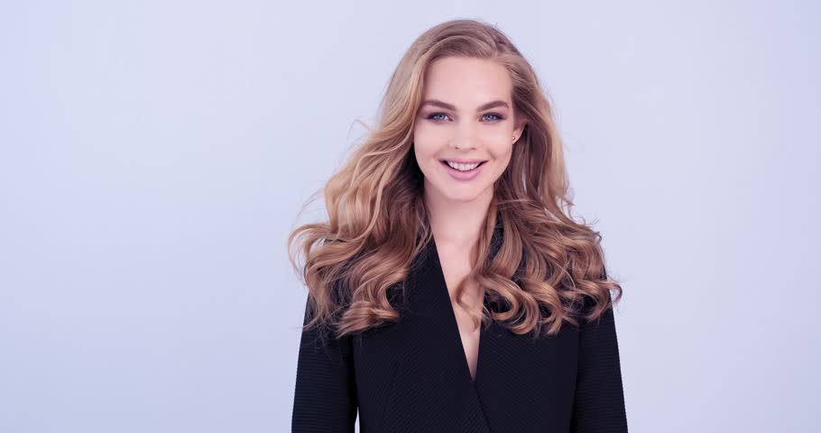 4K footage of a happy young blonde woman with curly long hair. Cheerful fashion model looks to the camera. Portrait of a  smiling face of a caucasian girl. Joyful model in black jacket. Slow motion.