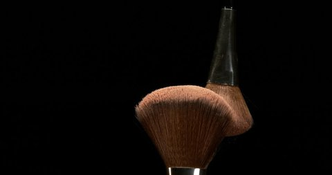 Make-up Brush spreading blush powder on black background, Slow motion 4K