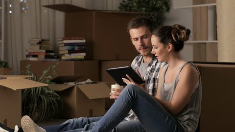 Happy couple moving home planning reform using a tablet sitting on the floor in the night