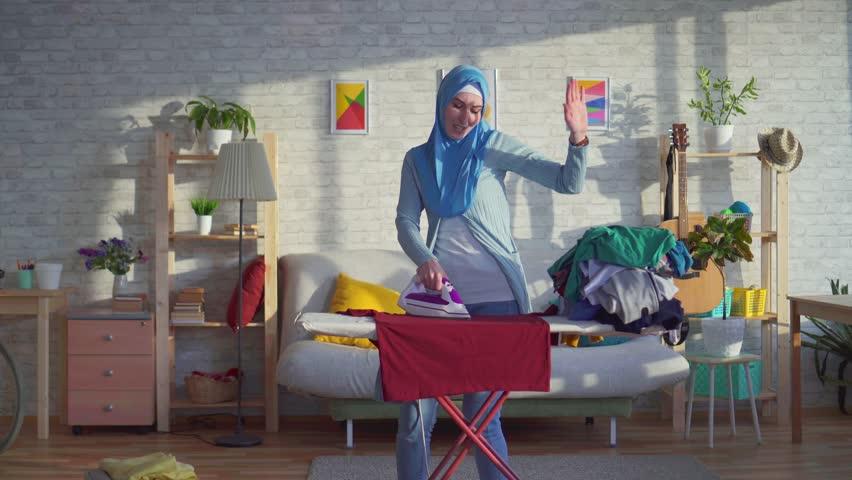 Beautiful Muslim woman cheerful dancing housewife | Shutterstock HD Video #1027894838
