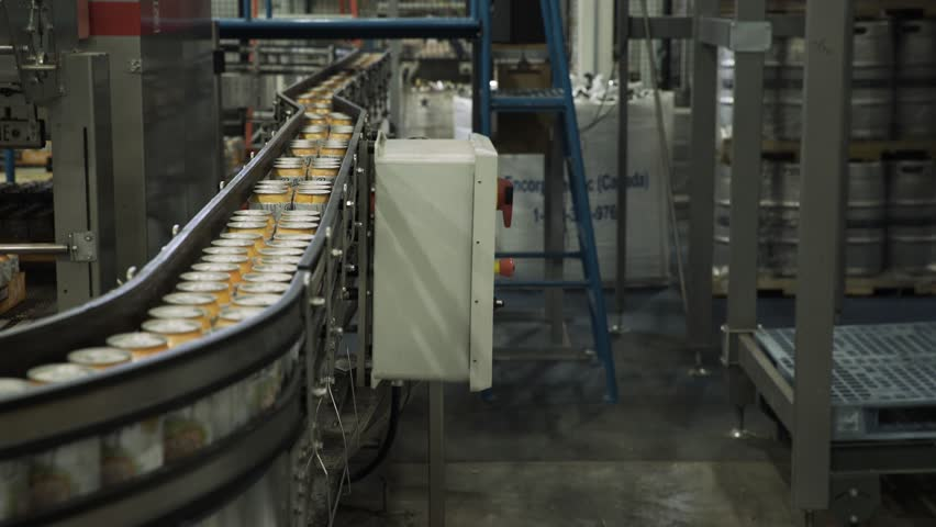 Aluminium cansing through converyor belt in packaging factory | Shutterstock HD Video #1027908728