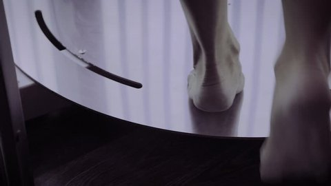 A woman walks into a solarium, legs closeup.