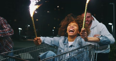 Slow motion close up of group of young friends of different ethnicities are having fun together racing on shopping carts and sparklers at supermarket parking at night.