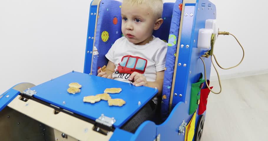 A little boy sits in a development car and eats cookies. A functional Montessori toy. Fine motor skills. Sensory sensitivity.   Shutterstock HD Video #1027920818