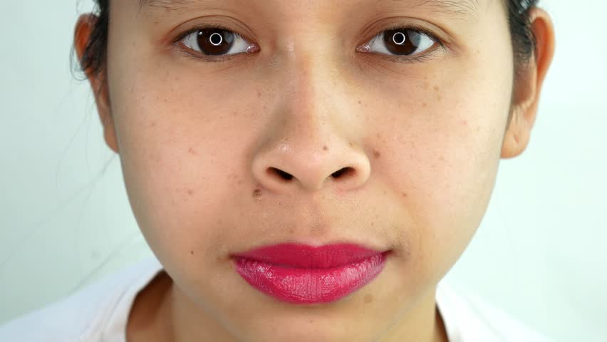 Shot of Asian young woman is blinking eyes and looking the camera .   Shutterstock HD Video #1027928648
