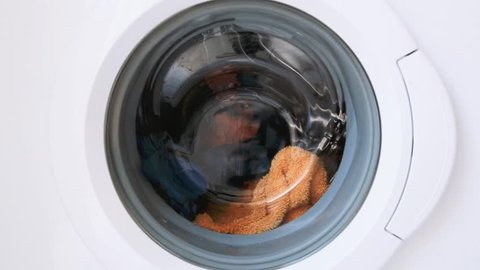 Home style footage. No sound. Forty 40 seconds of the clothes tumbling clockwise and anticlockwise in a front load washing machine, Includes orange towel, spotted garnment, red tshirt, check shorts.