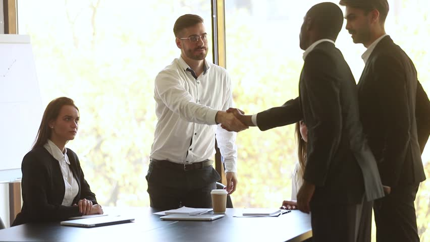 Company representative handshake diverse partners introducing coming at group meeting, caucasian businessman shake hands welcome african negotiator get acquainted express respect start negotiation