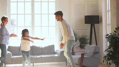 Happy cute blindfolded kid girl playing hide and seek activity catching parents mom dad in living room, little child daughter having fun laugh enjoy tag touch game with family mother father at home