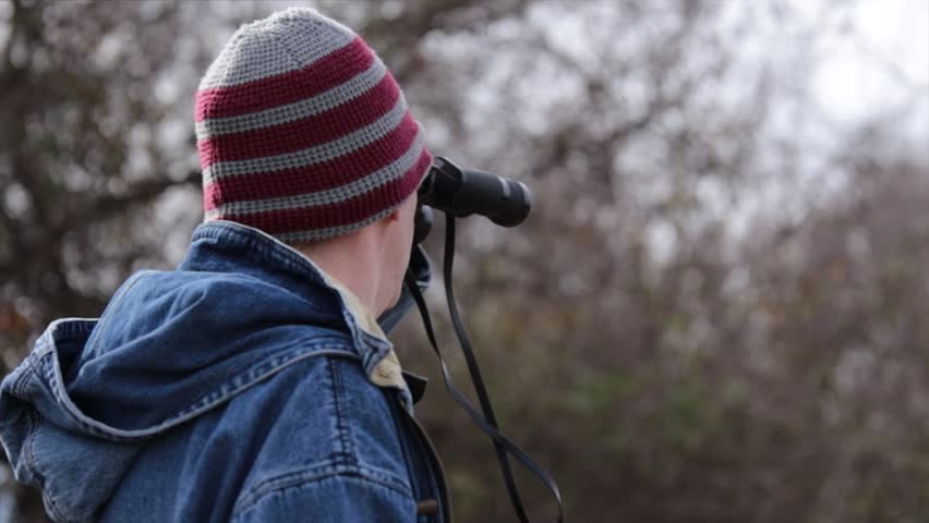 Young man wearing a denim jacket and knit cap looking through a pair of binoculars in a field on a cold autumn day | Shutterstock HD Video #1028047538