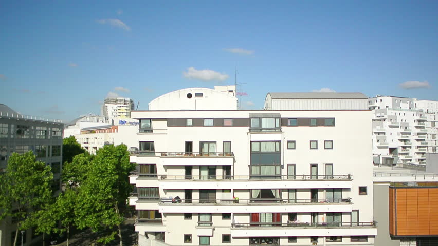 View from the flying drone of Parisian cityscape aerial with office buildings windows, apartments buildings, warehouses, supermarkets construction crane and clear blue sky