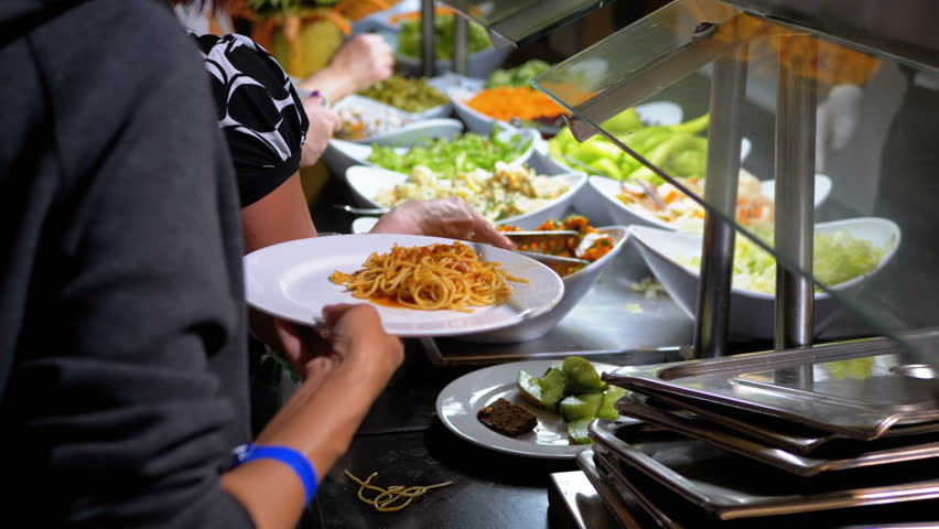 Ready to Eat Meals on the Counter in Dining Room Self-service. Buffet. People with plates choose their dishes. Dining at the hotel of Egypt. Various Food is sold on the counter in the cafe. | Shutterstock HD Video #1028094158