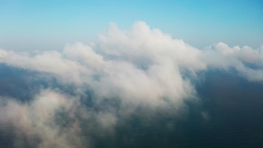 Scenic aerial view of moving white clouds. The drone is flying high in the blue sky through the fluffy clouds ahead. The sun is hidden behind the clouds. Ready footage for your text and design | Shutterstock HD Video #1028102138