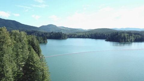 A vast aerial shot of a lake with blue skies and forest filled shorelines.