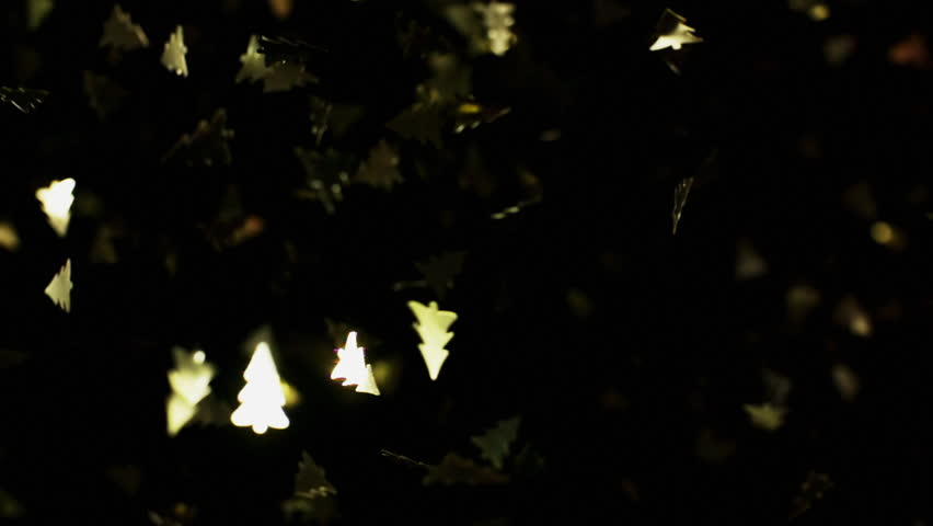 Golden christmas tree particles flying after being exploded, bright confetti bouncing against camera flying and falling down on black background. Top view close up slow motion | Shutterstock HD Video #1028119568