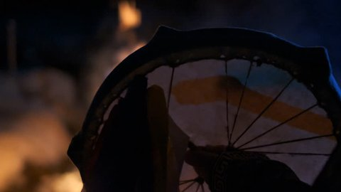 The silhouette of a shaman's tambourine near the fire.