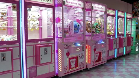 Kuala Lumpur,Malaysia - April 20,2019 : Panning view of the colorful arcade game toy claw crane machine where people can win toys and other prizes which is located in the shopping mall,Kuala Lumpur.