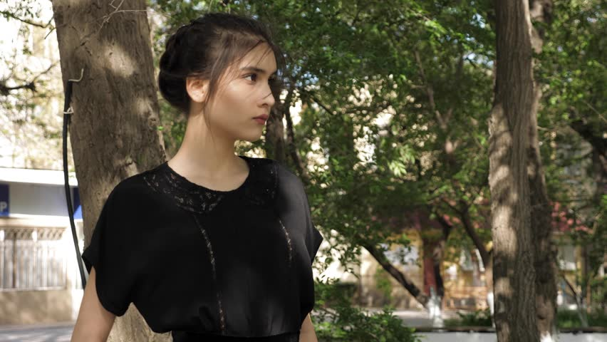 Beautiful young woman with hair bundle in nice black shirt with gentle lacy elements against waving green trees closeup | Shutterstock HD Video #1028136308