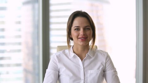 Head shot business woman looking at camera sitting at desk modern skyscrapers through window, coach talking making presentation use webcam sell products services, provide information or recording vlog