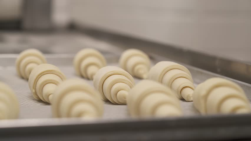 Left to right close-up shot of laminated dough rolled into croissants in the foreground. Pastry chef rolls viennoiserie dough to make a croissant. Professional food making concept   Shutterstock HD Video #1028141078